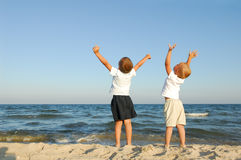 Freedom. Two boys on the beach with arms raised Stock Image