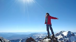 Freedom!. Girl over a snow capped peaks with outstretched arms Stock Photos