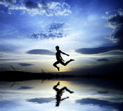 Freedom. A happy jump over a lake Royalty Free Stock Photo