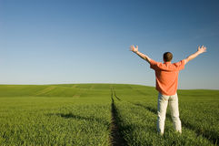 Freedom. Young men standing on green grass - arms outstretched Stock Images