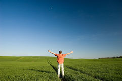 Freedom. Young men standing on green grass - arms outstretched Royalty Free Stock Photos