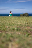 Freedom. Young girl is siiting on the grass and watching the ocean stock photos