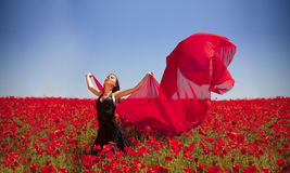 Freedom. Young pretty girl relaxing in the poppy field Stock Photo