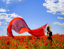 Freedom. Young pretty girl relaxing in the poppy field Royalty Free Stock Photography