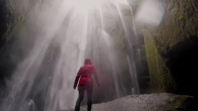 Freedom: back view of young woman standing on the rock near the Gljufrabui waterfall in Iceland and raising hands. Happy female enjoying the beautiful view of stock footage
