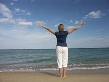 Freedom at the beach. Girl standing at the beach expressing joy of life Stock Image