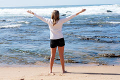 Freedom at beach. A young caucasian girl standing at the beach expressing joy of life with her arms open Royalty Free Stock Photography