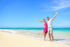 Freedom on beach vacation - happy carefree couple. Freedom on beach vacation - happy carefree winning couple with arms up showing happiness and fun on paradise Royalty Free Stock Images