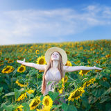 Freedom. Beautiful happy young woman on the sunflower field under summer sky with freedom emotions Stock Photo