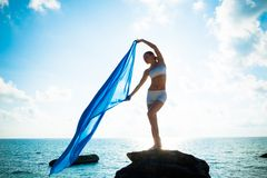 Freedom and Beauty concept. Beautiful girl with blue scarf standing on the Rock. Flying. Free. Vacation Royalty Free Stock Image