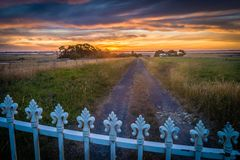 Freedom beyond the fence, sunset over a fence and trail Stock Image