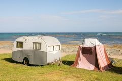 Freedom camping in vintage caravan and tent at an East Coast beach, Gisborne, North Island, New Zealand. Freedom camper in vintage caravan and tent on sand dunes stock image