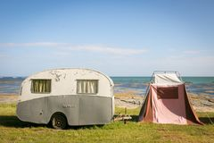 Freedom camping in vintage caravan and tent at an East Coast beach, Gisborne, North Island, New Zealand. Freedom camping in vintage caravan and tent on sand stock photo