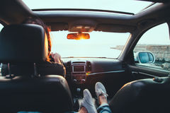 Freedom car travel concept. Fall car trip in sunset. Freedom travel concept. Spending weekend in roadtrip. Woman feet on car dashboard Stock Image