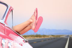 Freedom car travel concept - woman relaxing. With feet out of window in cool convertible vintage car. Girl relaxing enjoying free holidays road trip Stock Photos
