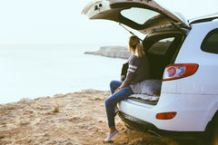 Freedom car travel concept. Woman relaxing inside car trunk and watching on sea. Fall trip in sunset. Freedom travel concept. Autumn weekend Royalty Free Stock Photos