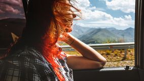 Freedom car travel concept - young woman relaxing out of window. Freedom car travel concept - young ginger woman relaxing out of window in a car. Road trip royalty free stock images