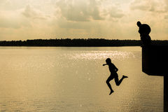 Freedom. Children jump to water,Silhouettes Stock Photos