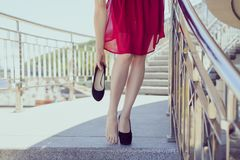 Freedom comfort foot-wear accessories concept. Close up view photo of classic cherry color burgundy maroon cocktail evening dress royalty free stock images