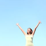 Freedom concept. Free woman smiling happy with arms raised joyful under clear blue sky. Beautiful young multiracial Asian / Caucasian girl in her 20s Stock Photos