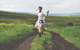 Freedom concept. Cheerful girl running on a countryside road. Toned image Royalty Free Stock Images