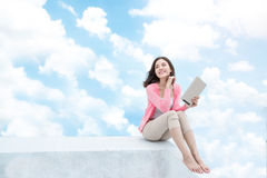 Freedom concept. Enjoyment. Asian young woman relaxing under blu Stock Images