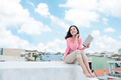 Freedom concept. Enjoyment. Asian young woman relaxing under blu Stock Image