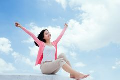 Freedom concept. Enjoyment. Asian young woman relaxing under blu. E sky on rooftop Royalty Free Stock Photos