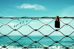 Freedom concept. image fence and old rusty lock and birds flying in the horizon. everything is possible. Freedom concept. image fence and old rusty lock and royalty free stock images