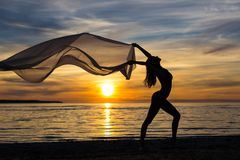 Freedom concept - silhouette of slim woman dancing with scarf on Stock Photos