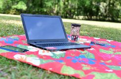 Freedom from the confinements of the cubicle and ofice. Laptop, coffee and cell phone displayed on an outdoor mat in nature representing freedom from the Royalty Free Stock Image