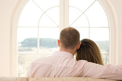 Freedom / couple. Couple sitting on the sofa in front of window/ Window on the world / freedom / new time Royalty Free Stock Images
