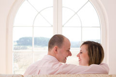 Freedom / couple. Couple sitting on the sofa and smiling/ Window on the world / freedom / new time Stock Image