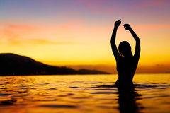 Freedom, Enjoyment. Woman In Sea At Sunset. Happiness, Healthy L Stock Photos
