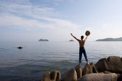 Freedom.Evening. The man stands on rocks and holds hat.Coast.Evening.Sunset Stock Images