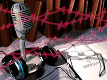 Freedom of expression. A little radio station, with its microphone and headphones close to it, and a opened book with glasses on it Royalty Free Stock Photo