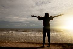 Women on the beach. Freedom extend the arms woman silhouette living a happy on the beach, female adult at holidays in Asia Thailand Stock Photos