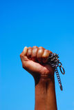 Black fist with chain. Black hand forming a fist with broken chain in front of blue sky background Royalty Free Stock Images