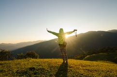 Freedom girl with hands up in the mountains Stock Image