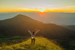 Freedom girl with hands up in the mountains stock images