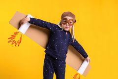 Freedom, girl playing to be airplane pilot, funny little girl with aviator cap and glasses, carries wings made of brown. Cardboard as an airplane. Studio Royalty Free Stock Photo