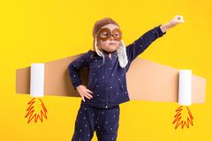Freedom, girl playing to be airplane pilot, funny little girl with aviator cap and glasses, carries wings made of brown. Cardboard as an airplane. Studio Stock Photography