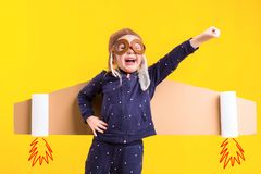 Freedom, girl playing to be airplane pilot, funny little girl with aviator cap and glasses, carries wings made of brown Stock Photos
