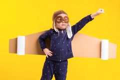 Freedom, girl playing to be airplane pilot, funny little girl with aviator cap and glasses, carries wings made of brown Stock Images