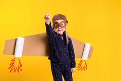 Freedom, girl playing to be airplane pilot, funny little girl with aviator cap and glasses, carries wings made of brown Royalty Free Stock Photos
