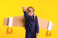 Freedom, girl playing to be airplane pilot, funny little girl with aviator cap and glasses, carries wings made of brown. Cardboard as an airplane. Studio Royalty Free Stock Photos
