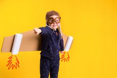 Freedom, girl playing to be airplane pilot, funny little girl with aviator cap and glasses, carries wings made of brown. Cardboard as an airplane. Studio Stock Image