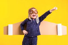 Freedom, girl playing to be airplane pilot, funny little girl with aviator cap and glasses, carries wings made of brown. Cardboard as an airplane. Studio Royalty Free Stock Image