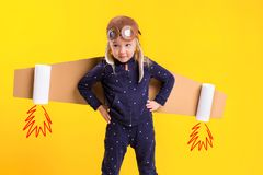 Freedom, girl playing to be airplane pilot, funny little girl with aviator cap and glasses, carries wings made of brown. Cardboard as an airplane. Studio Stock Photo