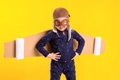 Freedom, girl playing to be airplane pilot, funny little girl with aviator cap and glasses, carries wings made of brown. Cardboard as an airplane. Studio Royalty Free Stock Photography